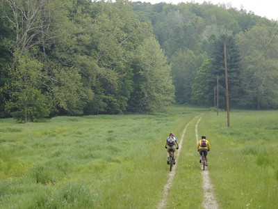 These mountain bikers ride down a solitary gravel road after a ride in the Hoosier National Forest near Story, IN.
