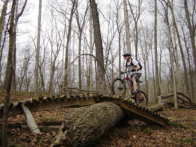 This mountain biker navigates a wooden bridge over a fallen tree on the Hesitation Point Trail in Brown County State Park near Nashville, IN.